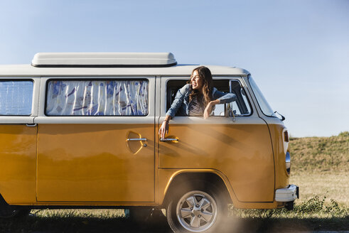 Pretty woman on a road trip with her camper, looking out of car window - UUF16131