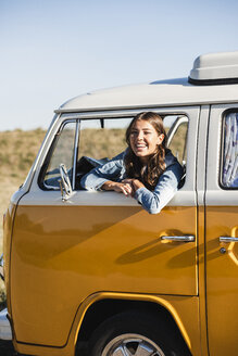 Pretty woman on a road trip with her camper, looking out of car window - UUF16134