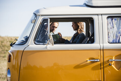 Couple on a road trip in their camper, looking at map - UUF16140