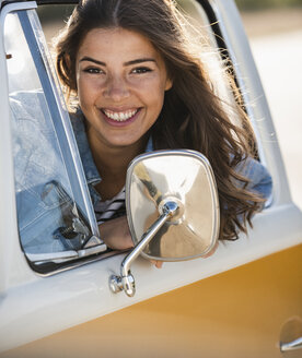 Pretty woman on a road trip with her camper, looking out of car window - UUF16155