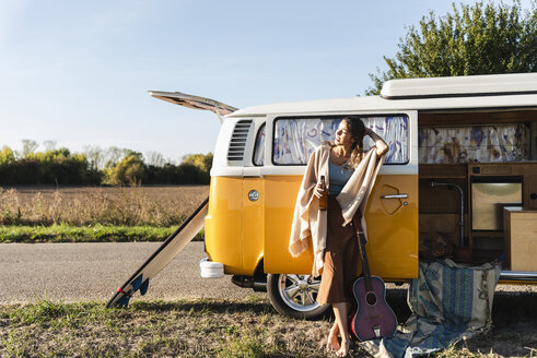 Pretty woman on a road trip with her camper, drinking beer, holding guitar - UUF16182