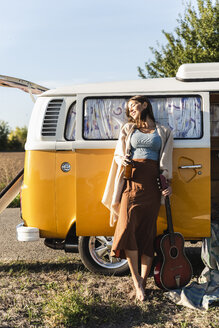 Pretty woman on a road trip with her camper, drinking beer, holding guitar - UUF16185