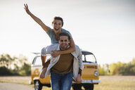 Happy couple doing a road trip with a camper, pretending to fly on the road - UUF16203