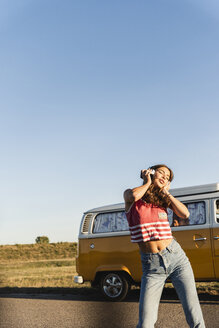 Pretty woman on a road trip with her camper, dancing, listening music - UUF16233