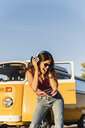 Pretty woman on a road trip with her camper, dancing, listening music - UUF16236