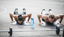 Sportive man and woman during pushups - HMEF00159