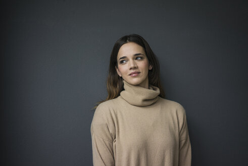 Portrait of smiling woman wearing light brown turtleneck pullover leaning against grey wall - MOEF01824
