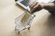 Woman's hand holding mini shopping cart with credit card - MOEF01827
