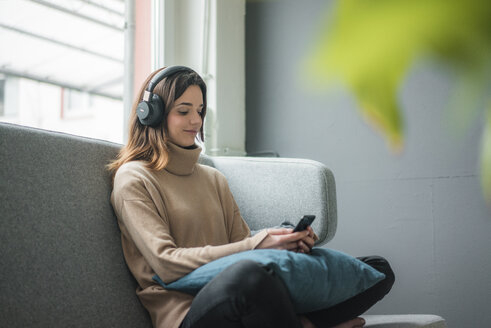Smiling woman relaxing on couch with smartphone and cordless headphones - MOEF01836