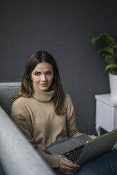 Portrait of content woman wearing light brown turtleneck pullover sitting on couch with laptop - MOEF01839