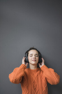 Portrait of woman wearing orange knit pullover leaning against grey wall listening music with headphones - MOEF01845