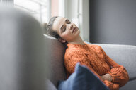 Portrait of woman wearing orange knit pullover having a break on the couch - MOEF01848