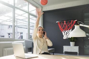 Freelancer on the phone throwing basketball into hoop in a loft - MOEF01857