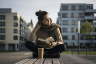 Melancholy woman with coffee to go and book sitting on bench in autumn - MOEF01863
