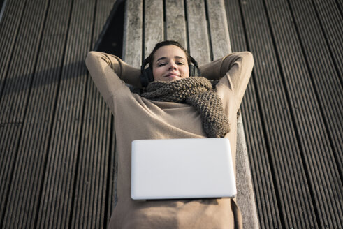 Portrait of smiling woman lying on bench listening music with cordless headphones - MOEF01866