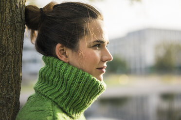 Profile of relaxed woman wearing green turtleneck pullover leaning against tree trunk - MOEF01875