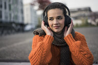 Portrait of woman wearing scarf and orange knit pullover outdoors listening music with cordless headphones - MOEF01878