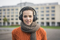 Portrait of smiling woman wearing scarf and orange knit pullover listening music with headphones - MOEF01881