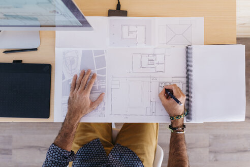 Close-up of architect working at home on floor plan - JRFF02169