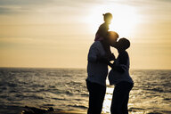Silhouette man kissing wife while carrying daughter on shoulders at beach during sunset - CAVF58027