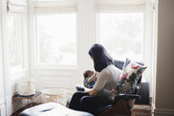 Side view of mother breastfeeding daughter while sitting by window on chair at home - CAVF58063