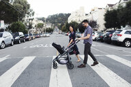 Parents with daughter in baby stroller walking on city street - CAVF58069