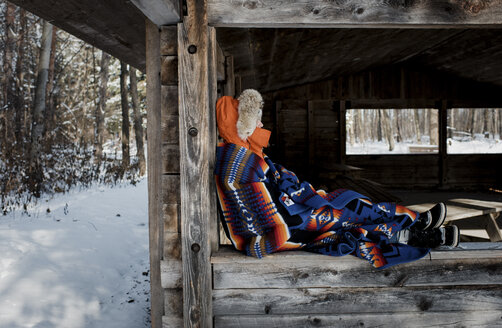 Side view of woman wrapped in blanket sitting on window at forest during winter - CAVF58090