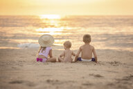 Rear view of siblings sitting on sand at beach during sunset - CAVF58264