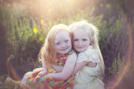 Portrait of cute sisters sitting on field during sunny day - CAVF58276