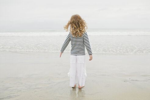 Rear view of carefree girl standing on shore against clear sky at beach - CAVF58282