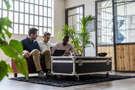 Three businessmen using laptop sitting on sofa in loft office - GIOF04971