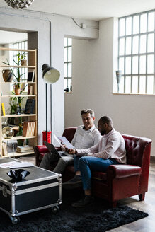 Two businessmen using laptop and discussing documents on sofa in loft office - GIOF04977