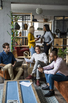 Business team having an informal meeting in loft office - GIOF04986
