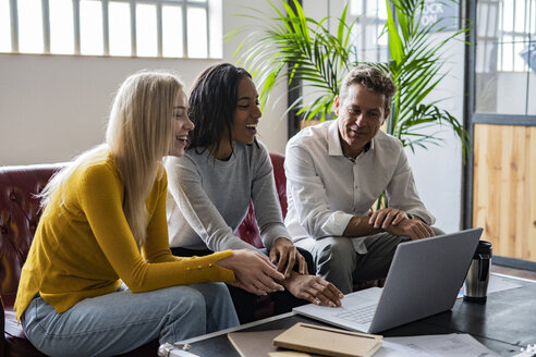 Happy business team using laptop sitting on couch in loft office - GIOF04995