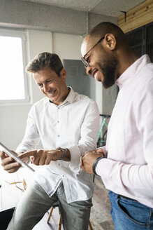 Two smiling businessmen with tablets having a meeting in loft office - GIOF05019