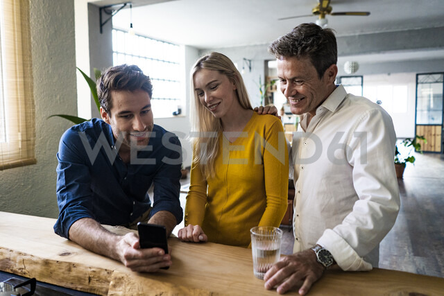 Smiling business team looking at cell phone together in loft office - GIOF05034 - Giorgio Fochesato/Westend61