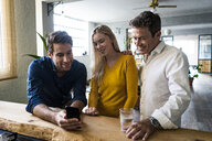 Smiling business team looking at cell phone together in loft office - GIOF05034
