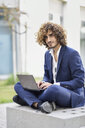 Portrait of young businessman with curly hair wearing blue suit sitting on bench outdoors using laptop - JSMF00650