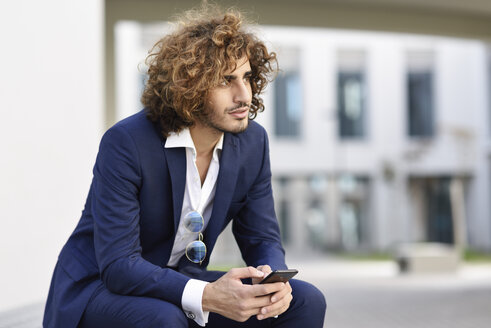 Portrait of young businessman with curly hair wearing blue suit sitting on bench outdoors - JSMF00656