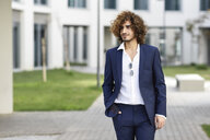 Portrait of young fashionable businessman with curly hair wearing blue suit - JSMF00659