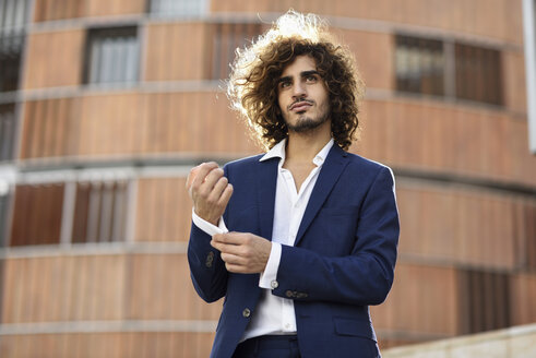 Portrait of young fashionable businessman with curly hair wearing blue suit buttoning cuff link - JSMF00668