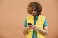 Smiling young man with curly hair wearing yellow waistcoat looking at cell phone - JSMF00674