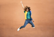 Happy young man with curly hair wearing waistcoat jumping in the air - JSMF00677