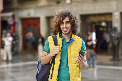Spain, Granada, portrait of smiling young tourist with backpack discovering the city - JSMF00680
