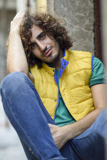 Portrait of smiling young man with beard and curly hair wearing yellow waistcoat - JSMF00689