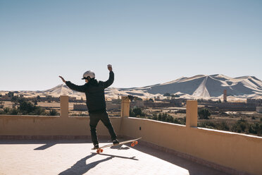 Rear view of man with skateboard on building terrace against clear sky - CAVF58293
