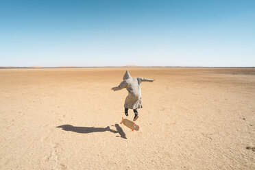 Rear view of man skateboarding on sand against clear blue sky - CAVF58296