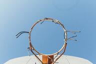 Directly below shot of broken basketball hoop against clear blue sky - CAVF58317