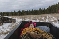 High angle portrait of teenage boy lying in off-road vehicle against sky during winter - CAVF58335