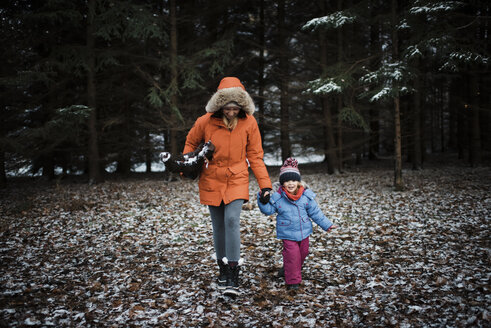 Mother and daughter in warm clothing walking at forest during winter - CAVF58347